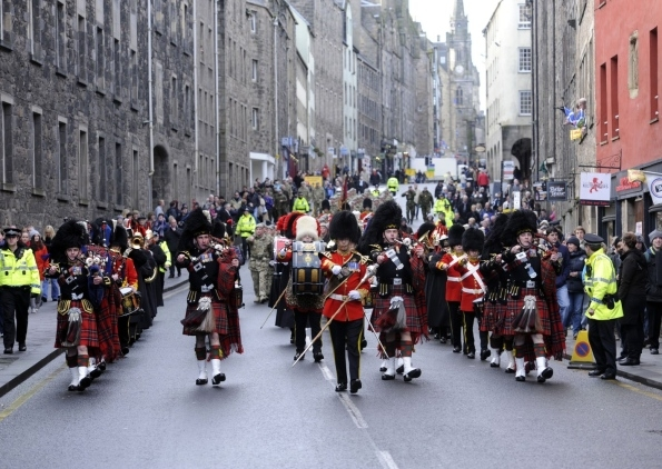 The Band, joined by the Pipes and Drums from the RSDG, march down the Royal Mile to Cannongate Kirk.